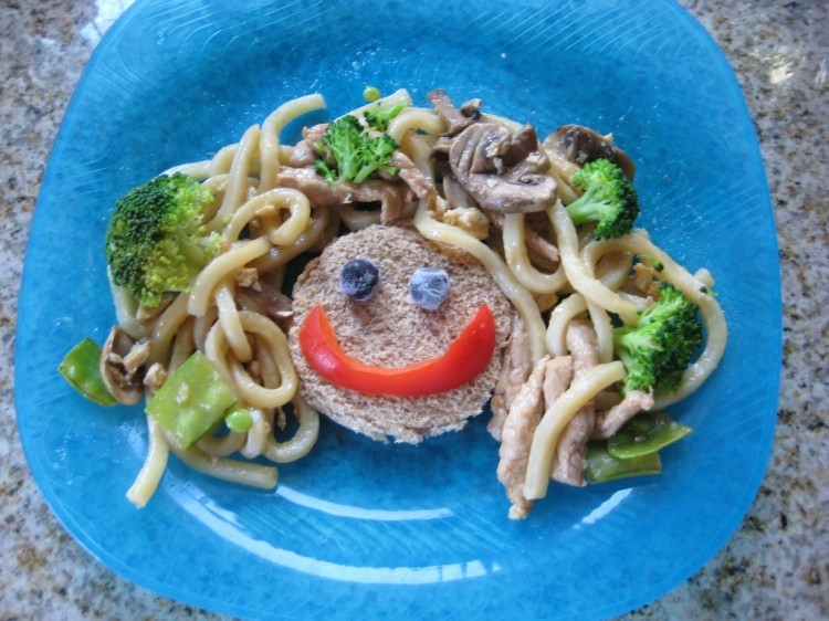 "Udon noodles with veggies and pork strips as ""hair""; bread circle with blueberry ""eyes"" and red pepper ""smile"""